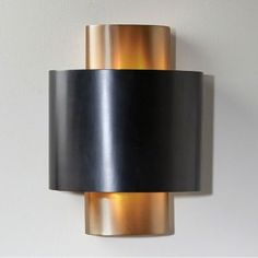 The Nordic Gold Wall Sconce offers a stylish solution to your lighting needs. A modern light fixture, with its cylindrical design, features a handsome, antique bronze-finished oval shade. Great addition to the living room, dining room, bedroom or office!