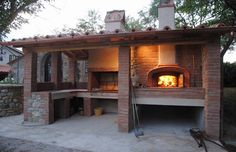 Covered outdoor kitchen with pizza oven and barbeque area.