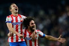Atletico Madrids midfielder Gabi (L) and Atletico Madrids Turkish midfielder Arda Turan celebrate after winning the Spanish Kings Cup (Copa del Rey) final football match Real Madrid vs Atletico de Madrid at Santiago Bernabeu stadium in Madrid on May 17, 2013. Atletico Madrid won the match 2-1. JAVIER SORIANO/AFP/Getty Images