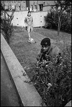 British soldier hides behind a bush while a woman mows her lawn in Northern Ireland 1973 Photograph: Philip Jones