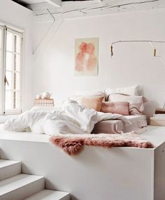 White bed with plush and fur pink accents