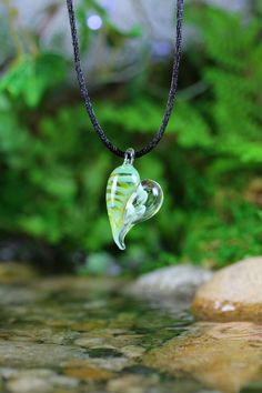 String necklace with black and gold stripe glass pendant in the shape of a heart.
