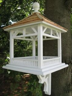 """DESCRIPTION: Fly-through Dream House gazebo feeder is perfect for just about any setting. Constructed from exterior grade ply-board and topped with pine shingles. Large open area can be used with seed or easily accommodate a piece of fruit for Orioles to enjoy. Comes with mounting bracket DIMENSIONS: 15""""H x 10.5""""W x 10.5""""D SHIPPING: Please allow 2 -9 business days for delivery"""