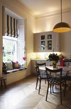 White kitchen with a lovely window seat, dramatic pendant lamp and gorgeous wood floors.