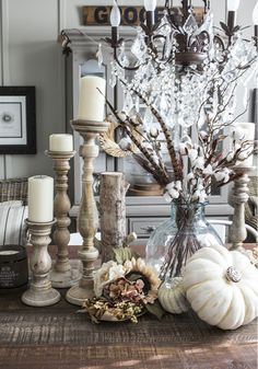 Cotton boll branches pheasant feathers white pumpkins and white washed candle holders love!
