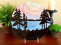 Abstract landscape acrylic pour painting, with silhouetted trees, all on a vinyl record.