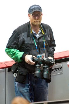 """3D Nikon - He has what appears to be two Nikon D700 cameras """"glued"""" together with a 24-70mm f/2.8G attached"""