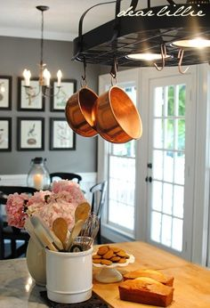 Grey wall, black details, black counter tops white cabinets,..Copper Pots