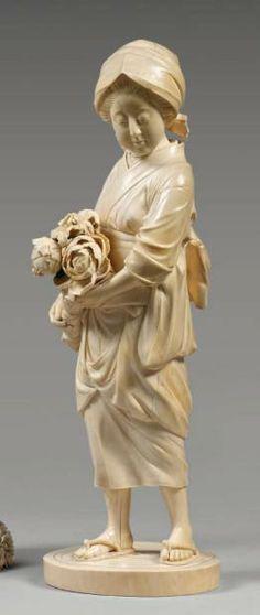 JAPON - Epoque MEIJI (1868 - 1912), Okimono en ivoire, jeune femme debout portant un bouquet de pivoines et de lys. Signé Akigyoku ?