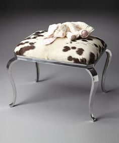 This rustic yet modern ottoman showcases faux cowhide upholstery and nickel cabriole legs to add eye-catching appeal to your sophisticated abode.