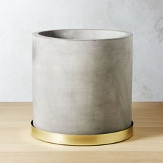 Shop moda cement planter.   Earthy cement round roots plants in an industrial chic fashion.  Crafted with a drainage hole, matt egrey planter rests on a metallic gold tray meant to catch excess water.  We can't get enough of this modern mix of materials.