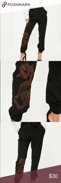 """Missguided black snake print embroidered joggers - be a boss babe and look fierce in these joggers - featuring snake print embroidery in a rust orange hue, crepe fabric, cuffed ankles and a satin waistband with front drawstring.   regular / stretch fit - elasticated waistband   100% polyester   approx inner leg length 70cm/27"""" (based on a uk size 8 sample)   stella wears a uk size 8 / eu size 36 / us size 4 and her height is 5'5""""   product number: r9335208 hand wash no trades Missguided…"""