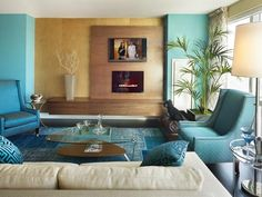 The patchwork style of the overdyed rug mimics the graphic shapes of the turquoise accent wall in this colorful living room. Design by Gacek Design Group