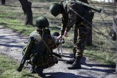 Russian soldiers, who are carrying grenade launchers, pet a stray dog near a Ukrainian military base in the town of Bakhchisarai in the Crimea, on March 3, 2014. (Photo by Sergei L. Loiko/Los Angeles Times/MCT)