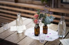 Amber bottles with natural flower arrangement and vintage linen decorate the tables for Steph and Martin's rustic cafe wedding