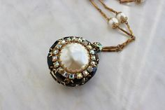 Vintage pearl pendent necklace black rhinestones 1960s large. Gorgeous, over sized pendent necklace featuring a 2 sided pearl faced jewel surrounded by jet black and aurora borealis rhinestones! This is a very unusual piece as I have never seen another one like this! It has never been worn. In excellent condition! Clasp is in good working order.  Vintage pearl and rhinestone pendent necklace Gold tone, with round shaped pendent - very 3 dimensional Pendent is 2 sided: domed pearl jewel and…