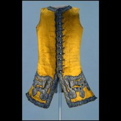 "Waistcoat, England, 1745-1760. Bright yellow silk satin, trimmed down fronts, hems, and around pocket flaps with 1 1/2"" wide silver tinsel woven tape or galloon."