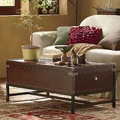 "Voyager Coffee Table  Add old-world flair to new spaces with the Voyager Coffee Table. Transitional in style, it offers a dash of antique flavor that will blend seamlessly with your other furnishings. Hinged top opens up to reveal valuable storage inside. Gunmetal gray hardware. Metal legs; black painted finish. Composite wood; rich, brown stained finish. Assembly required. 42"" l x 24"" w x 18 1/4"" h. www.countrydoor.com"