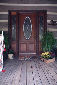 A rustic Fall log cabin porch with purple and yellow mums and plaid