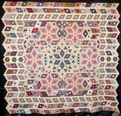 This quilt was named Honeycomb (Rayon de miel) by its maker, Liliane Verger of Royan, France.  It was inspired by an English quilt in a book by Diana Lodge; quilts such as these were much appreciated in England in the Victorian age (circa 1840).  The hexagons were all made using the English paper method.