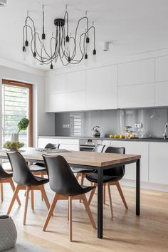 Simple white kitchen with clean lines, and rustic dining table with lights to create a contemporary cool look