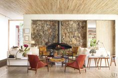Living room: a quartet of vintage armchairs—by Ib Kofod-Larsen, foreground, and George Nakashima, rear—are gathered near a 1960s French fireplace by Focus. The twin side tables are by Paul McCobb, the fireplace wall is of stacked quartzite, and the ceiling and floor are sheathed in bleached hardwood.