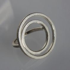 Big contemporary statement ring .    When wearing the ring it seems like two circles floating over the hand.    This ring is made of sterling silver. It has a textured and oxidized surface with polished edges.    It is made of 2mm square wire and the diameter is ca. 3 cm.    It´s like an object on the hand because you dont see the ring band.    I can make it in any size, just let me know in a massage to seller the size you need ,when you make the purchase.    If you have any question please…