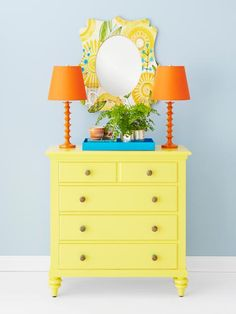 """A sunshine yellow dresser finds an equally upbeat partner in a curvy mirror patterned with huge, happy blossoms. Also cheerful: bright tangerine lamps—so compact, there's room enough for two—a vivid turquoise tray, and painted wood knobs. Mirror: Cori Dantini Sun Burst Flowers quatrefoil 28"""" x 23"""" mirror, $149, denydesigns.com Dresser paint: Cheerful by Benjamin Moore Wall paint: Oatlands Dainty Blue by Valspar"""
