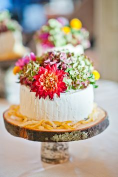 too many flowers, but i like the little white simple cake on the tree stand. nice look