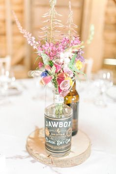 Gin Bottle Flowers Centrepiece Table Log Slice Rustic Summer Country DIY Barn Wedding http://sarahjaneethan.co.uk/