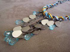 Maxi colar confeccionado em corrente de metal prata velha entrelaçada com fios de cera nas cores azul claro, lilás e amarelo. Pingentes em gotas de metal na cor prata e gotas acrílicas transparentes na cor azul claro.  Dimensões: Comprimento: 48cm + 7cm de corrente extensora para regulagem de altura Pingente: 10cm de comprimento no total R$74,90