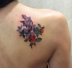 Illustrative lilac and blueberry tattoos on the right shoulder blade.