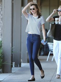 Miranda Kerr wears a striped t-shirt, high-waisted jeans, flats, and round sunglasses