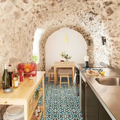Homeowners added only small, modular furniture and appliances to keep from overwhelming this kitchen's ancient stonework. | Coastalliving.com
