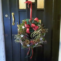 Natural, mossed door wreath with cones, grasses, air plants, stars and a red and green ribbon. Christmas Flowers, Christmas Wreaths, Christmas Arrangements, Table Centers, Green Ribbon, Grasses, Air Plants, Door Wreaths, Bouquet