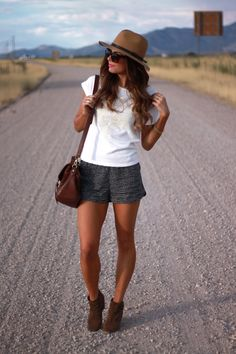 white graphic tee, black printed shorts, brown bag, brown booties and brown hat.