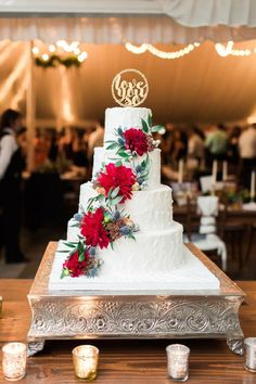 Four tiered white buttercream wedding cake. Cascading red cake flowers and gold cake topper.