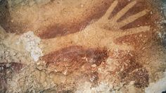 Hand stencils from the Indonesian island of Sulawesi have been dated to at least 40,000 years old. Photo - Kinez Riza.