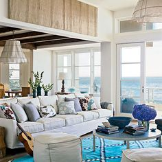 Beach-Chic    The sofa pairs with a round, ocean-blue tiled coffee table to accommodate big groups. Linen-wrapped poufs make for extra, moveable seating. Wood lamps and a wire-and-linen chandelier cast soft light on the space.