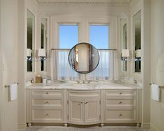 An elegant cream vanity with a gorgeous marble countertop is nestled under two windows with a beautiful water view in the master bathroom. A small, round mirror is situated between the two windows so as not to block the view.