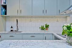 Vackra köksluckor i Lindblomsgrönt med beslag i läder och krom. Den vackra bänkskivan i marmor matchas av vitt kakel på väggen ovan   Ballingslöv