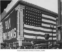 Businesses all over the country sold war bonds to help pay for World War II. This photo, taken outside Seattle's Frederick & Nelson department store, shows a large bond ad and an American flag displayed on the building. Frederick & Nelson won awards for selling large numbers of bonds, ca. 1943.