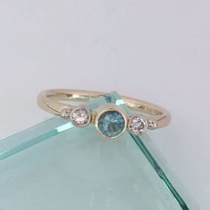 Ocean blue, classic, 4mm round faceted Maine tourmaline set in a yellow gold bezel, hugged by 7pt brilliant cut diamonds. -- Harvest Gold #MadeInAmerica