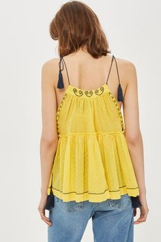 Opt for a boho look this season in yellow navy embroidered camisole top with a hanky hem. Team with light wash jeans and sliders for a summer feel.