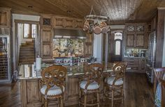 High Country Cabinets| Cabinets| Boone NC| Banner Elk NC.  Mountain home with old world charm.  Knotty Alder kitchen with stained and distressed cabinetry.  Many of the stacked cabinets have glass with decorative X mullions.
