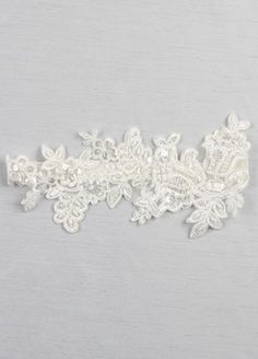"This elegant bridal garter is a beautiful way to add chic style to your wedding. A floral patterned applique is delicately beaded with faux pearls and sequins and is sewn to velvet stretch elastic. Features and Facts:  Single Garter  Measures 16"" around unstretched Lace applique measures 5"" width, 11"" length"