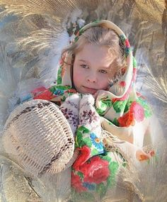 A girl is dressed in traditional Russian shawl with bright floral ornament.