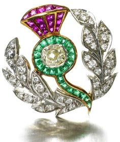 A fine early 20th Century ruby, emerald and diamond thistle brooch The stem and thistle head with a row of trapezoid-cut emeralds, with an old oval-cut diamond to the centre, the flower set with French-cut rubies, the leaves set with round brilliant-cut diamonds, mounted in two colour gold, the main diamond estimated to weigh approximately 0.31ct