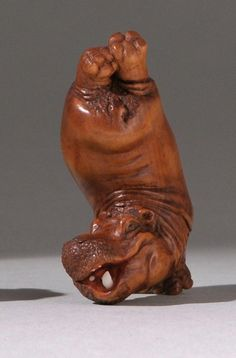 """WOOD NETSUKE Contemporary By Kozan. Depicting a comic hippopotamus with inlaid teeth balancing on his front legs. Signed in seal form. Height 2"""" (5 cm)."""