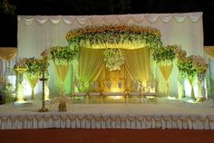 Reception stage at Narayana Lawns & Banquets Mumbai. Sunshine yellow drapes and blossoms, with decorative gold chairs. Indian Wedding Stage, Wedding Stage Design, Reception Stage Decor, Wedding Reception Backdrop, Wedding Hall Decorations, Marriage Decoration, Decor Wedding, The Wedding Planner, Wedding Planners